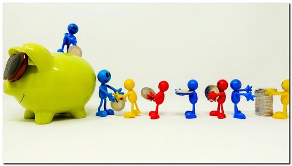 カラフルな複数の人形がお金を貯金箱に運んでいる画像